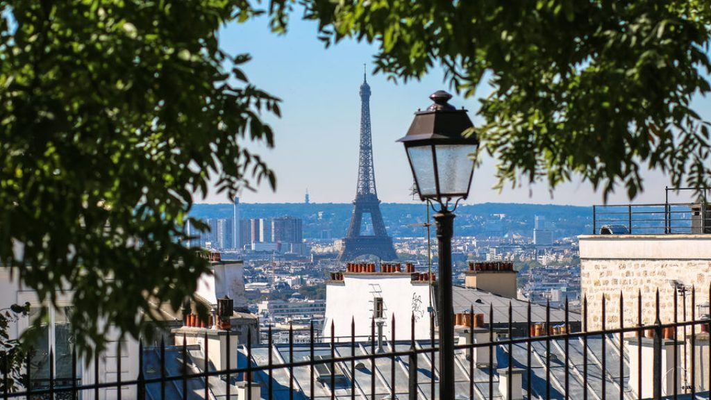 the Eiffel Tower from a distance with a lamp post and tree branches in the foreground