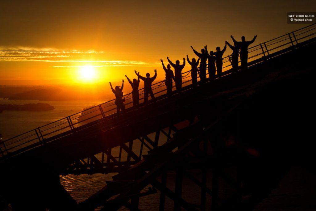 People climbing the Sydney Bridge at sunset