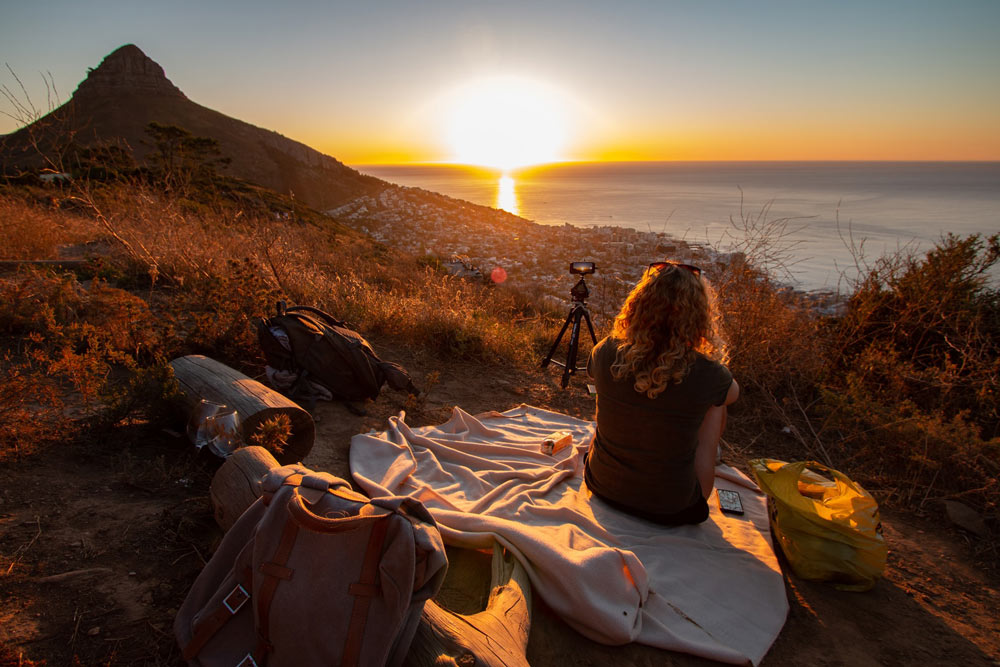 Woman seated on signal hill at sunset