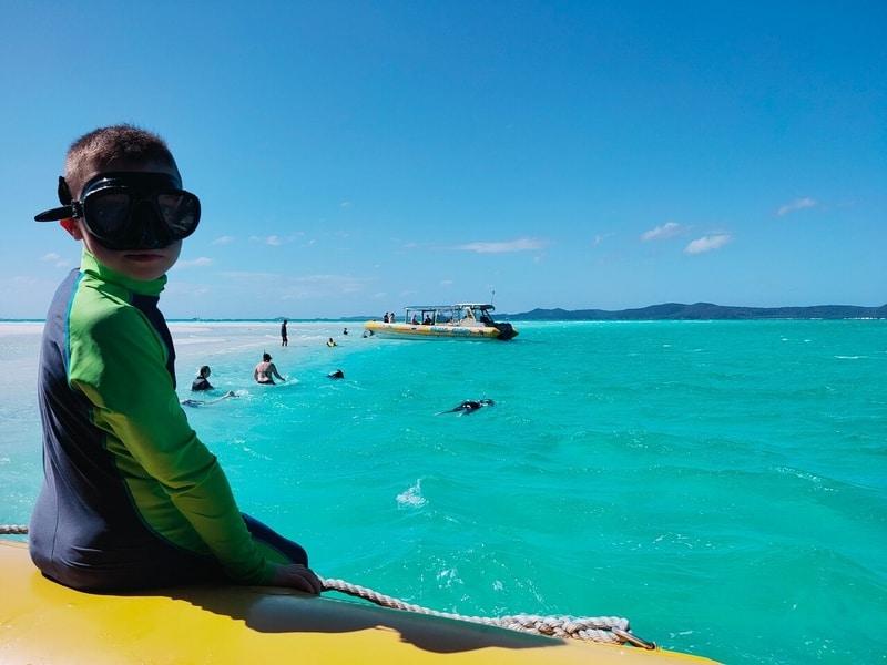 boy sitting on boat snorkeling