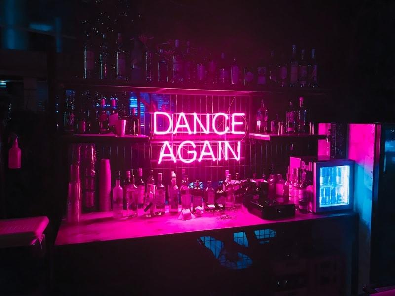 "Pink neon ""DANCE AGAIN"" Lights along the wall of a bar"