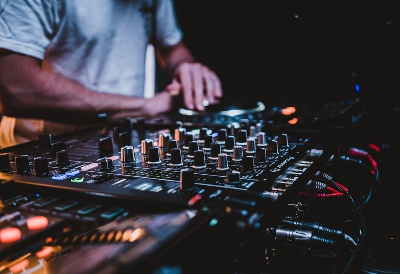 A nightclub DJ playing a set using his deck