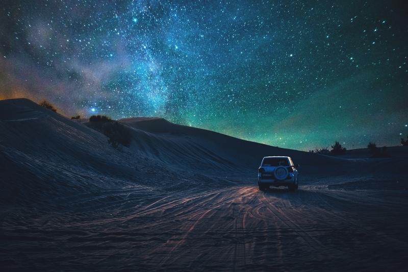 Car in Dubai desert at night
