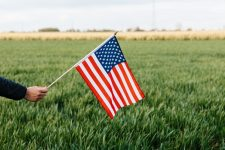 Person holding the US flag in a field