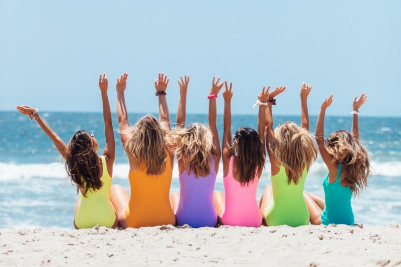 Six women on the beach throwing their hands in the air
