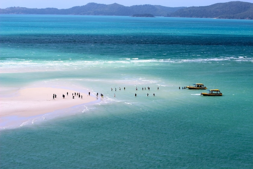 Two yellow motorized rafts parked against the shore of Whitehaven Beach with tourists on the beach