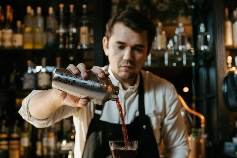 Bartender pouring wine in glass