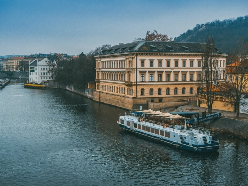 boat-on-prague-river-next-to-historical-building