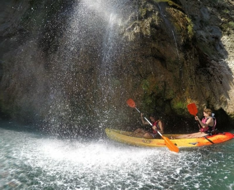 two people in a kayak under a waterfall in nerja malaga