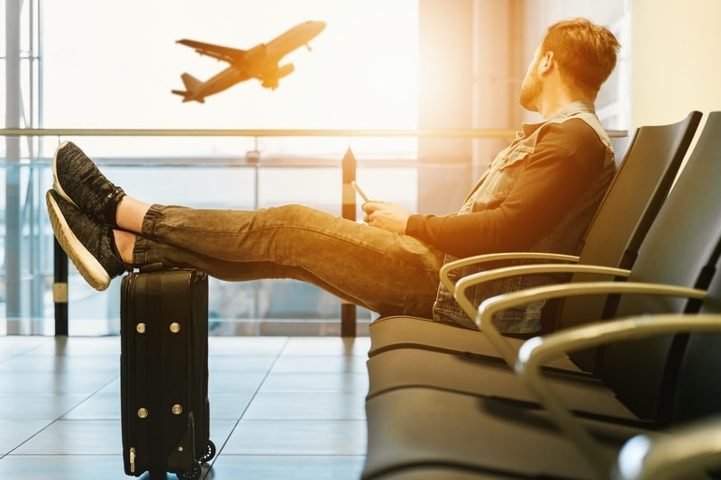 man-at-airport-watching-plane-leave