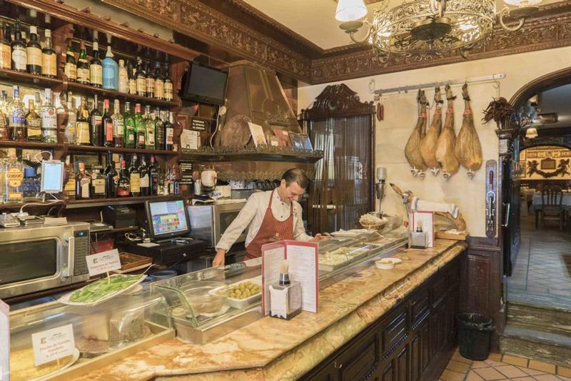 Smiling barman serving tapas