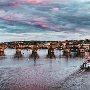 prague-river-cruise-boat-moving-towards-bridge